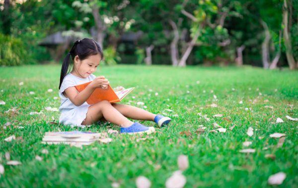 libros-recomendados-para-quinto-y-sexto-de-primaria-nina-en-el-parque-leyendo-istock
