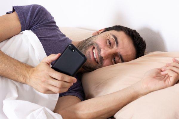 Hombre sonrie mirando movil en la cama