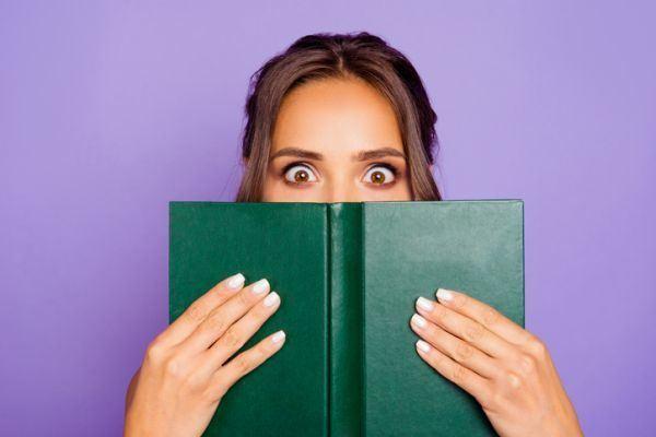 elementos-de-la-narracion-mujer-asombrada-por-libro-istock