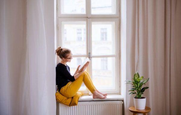 elementos-de-la-narracion-mujer-sentada-en-la-ventana-leyendo-istock
